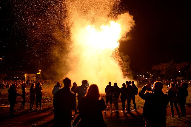 People gather to watch a bonfire burn in the Shankill Road area ahead of the Twelfth of July celebrations held by members of the Orange Order in Belfast