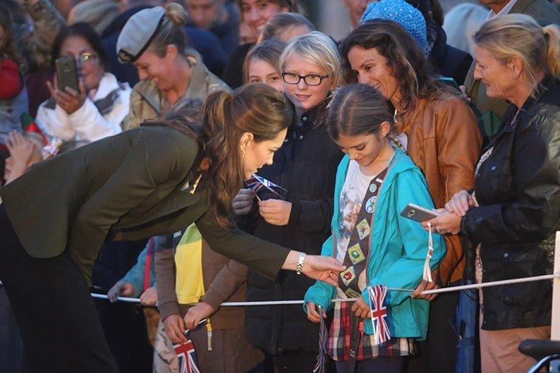 Duchess of Cambridge admires a young girl's sash