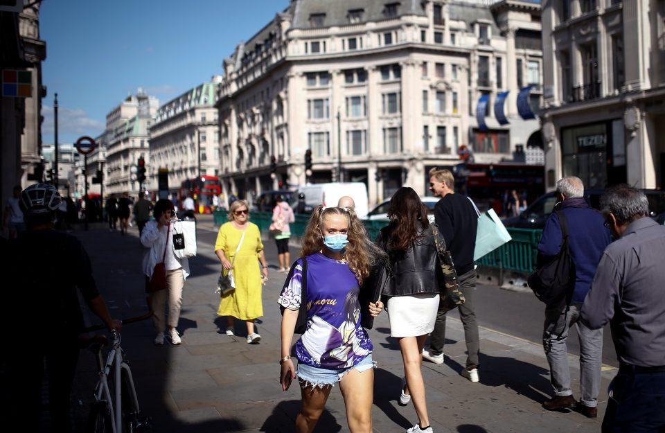 Pedestrians, Some Wearing Protective Face Masks, Walk Along Regent Street, Amid The Coronavirus Disease (covid 19) Outbreak, In London