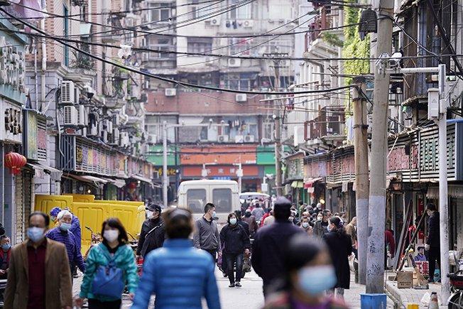 File Photo: People Wearing Face Masks Walk On A Street Market In Wuhan