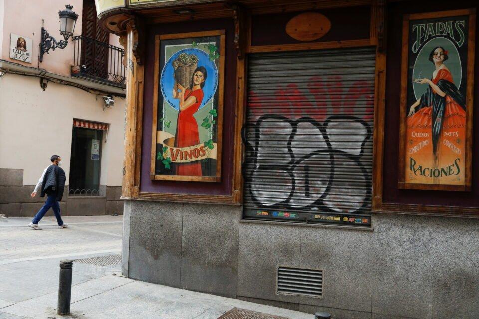 A man walks past a closed bar in Madrid
