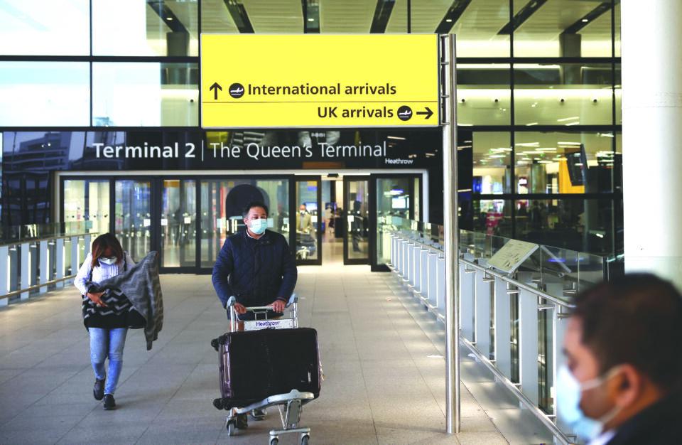 file photo: travellers walk through terminal 2 at heathrow airport, amid the coronavirus disease (covid 19) outbreak in london