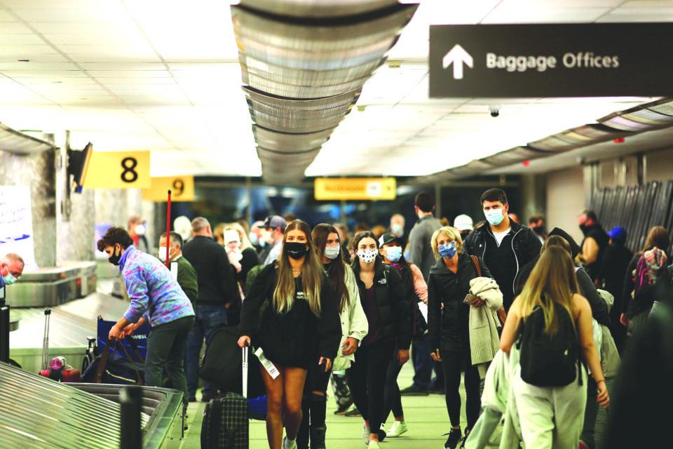 file photo: travelers reclaim luggage at denver airport
