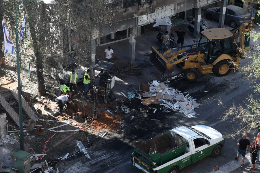 Israeli rescuers clean the rubble of a building directly hit by a rocket fired from the Gaza Strip, in central Israeli city of Ramat Gan, on May 15, 2021. (Gideon Markowicz/JINI via Xinhua)