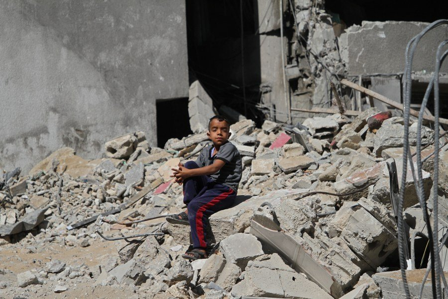 A Palestinian child sits on the rubble of a house destroyed by Israeli airstrikes, at the Shati refugee camp in Gaza City, May 15, 2021. (Photo by Rizek Abdeljawad/Xinhua)