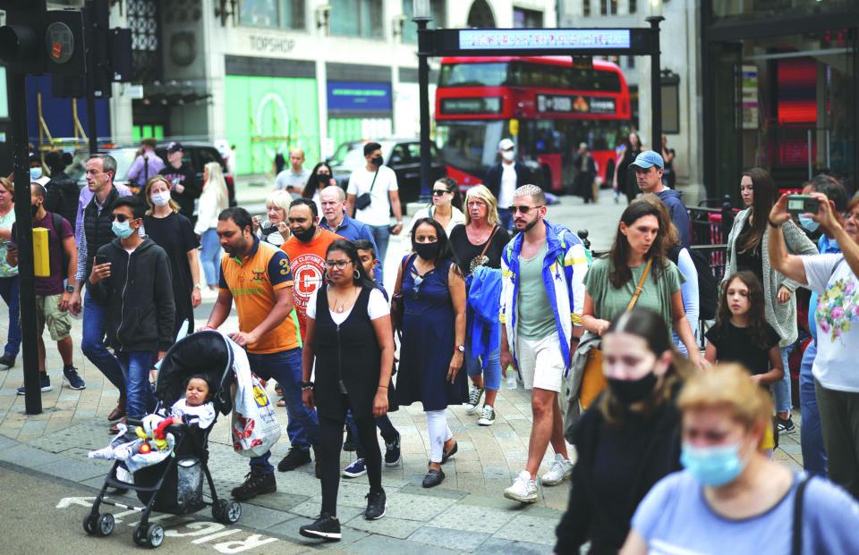people walk through oxford circus, amid the coronavirus disease (covid 19) outbreak, in london