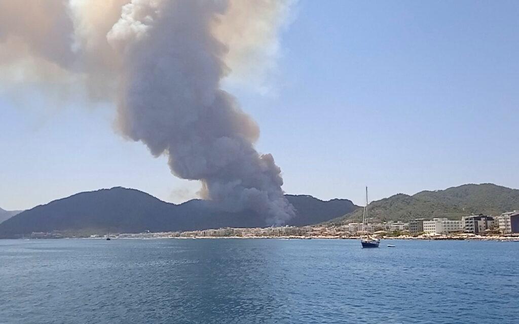 a plume of smoke fills the sky of the coastal resort of marmaris
