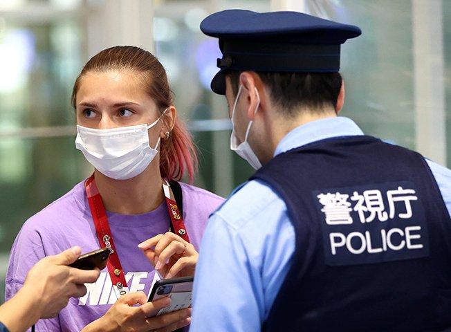 belarusian sprinter krystsina tsimanouskaya talks with police officers at haneda international airport in tokyo