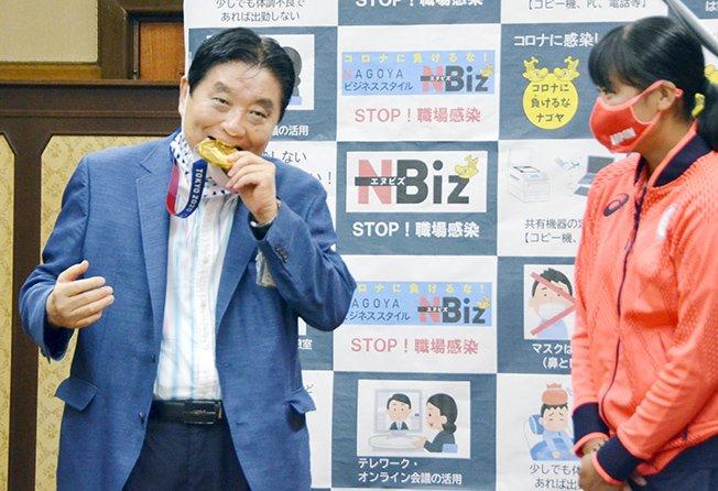 file photo: nagoya city mayor takashi kawamura bites the tokyo 2020 olympic games gold medal of the softball athlete miu goto in nagoya, japan